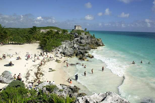 ** FILE ** Tourists enjoy the beach near the Mayan ruins of El Castillo, or The Castle, the main temple in the ancient Maya city of Tulum in Mexico's Yucatan peninsula in this Dec. 30, 2004 file photo. (AP Photo/Israel Leal/FILE)