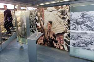 A propaganda poster of Adolf Hitler contrasts with photographs of victims of the Nazi era at the entrance to the documentation center on the Third Reich on Obersalzberg mountain in Berchtesgaden, Germany.