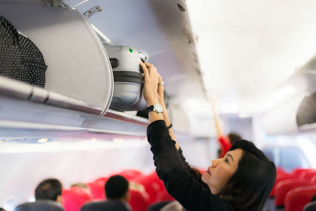 Air travel Putting small, personal bags in the overhead bins.
