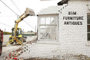 A backhoe tears into the former B&M Furniture and Antiques building at 1622 Bozza St. in Alton Monday, where the building was being razed and the debris hauled away.