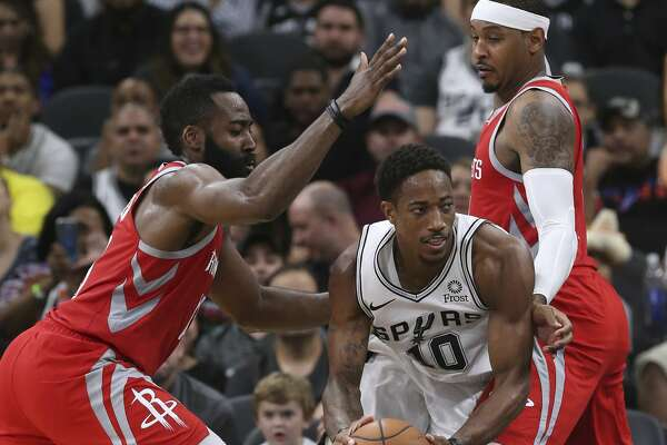 San Antonio Spurs' DeMar DeRozan gets between Houston Rockets' James Harden, left, and Carmelo Anthony during the second half at the AT&T Center, Sunday, Oct. 7, 2018. The Spurs lost 108-93.