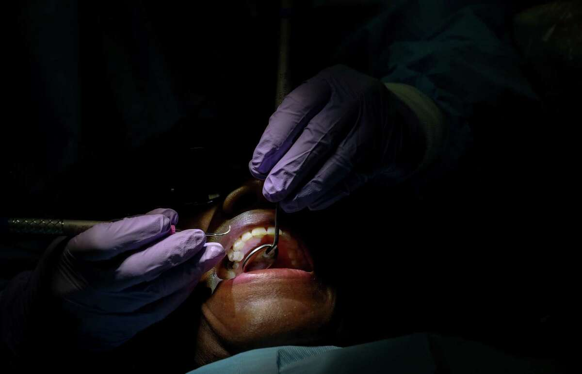 Dee Behn, a Marine veteran, has her teeth cleaned by Lisa Nguyen, a dental hygiene student, during an event at UTHealth School of Dentistry Friday, Nov. 9, 2018, in Houston. Behn has chipped teeth and a missing molar, and said it had been several years since she'd last seen a dentist.
