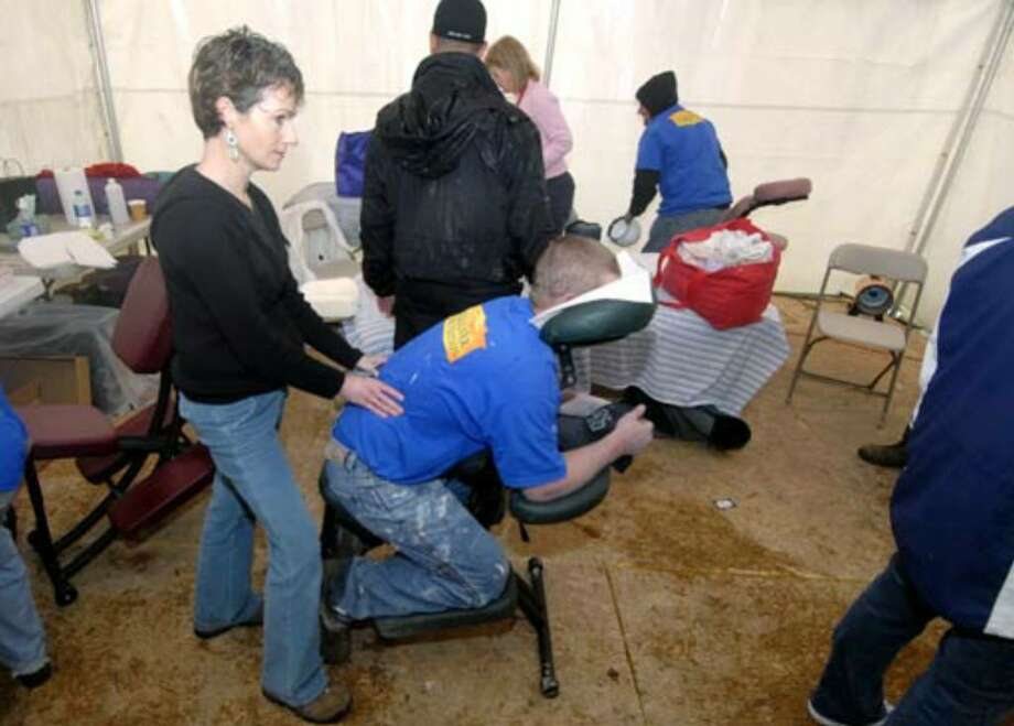 Colonie massage therapist Nancy Schramek, left, sooths the aching back of a volunteer during the rebuilding of the home during lunchtime on Monday, March 26. Photo: Skip Dickstein