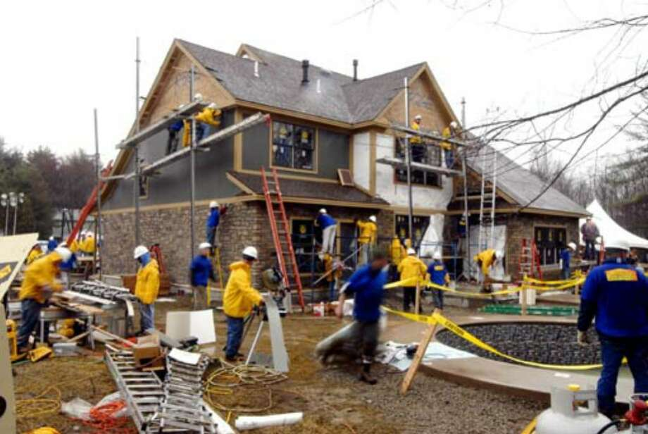 Construction crew outside Debbie Oatman's Fairway Lane home during lunchtime on Monday, March 26. Photo: Skip Dickstein