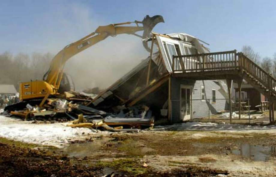 "The home of Debbie Oatman in Colonie is demolished on Saturday, March 24, 2007, as part of the television show ""Extreme Makeover: Home Edition."" Photo: Michael P. Farrell"