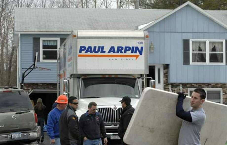 "Workers prepare the home of Debbie Oatman on Fairway Lane in Colonie on Friday, March 23, for demolition the next day so that a new house can be built as part of the television show ""Extreme Makeover: Home Edition."" Photo: Michael P. Farrell"
