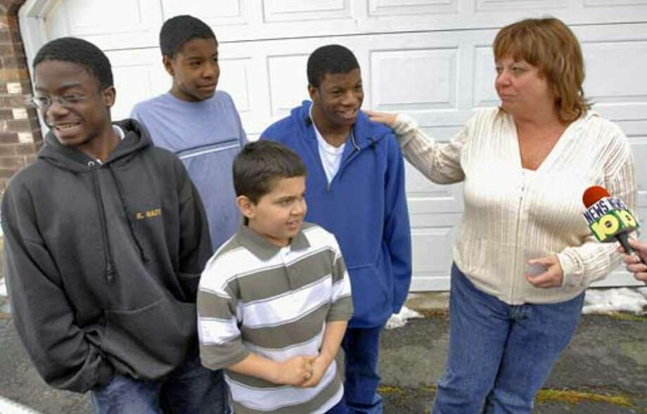 "Debbie Oatman stands with her sons, from left, Kevin, 16, Brian, 15, Scout, 10, and D.J., 20, outside their Colonie home during a break in filming for ""Extreme Makeover: Home Edition"" on Thursday March 22, 2007. Photo: Philip Kamrass"