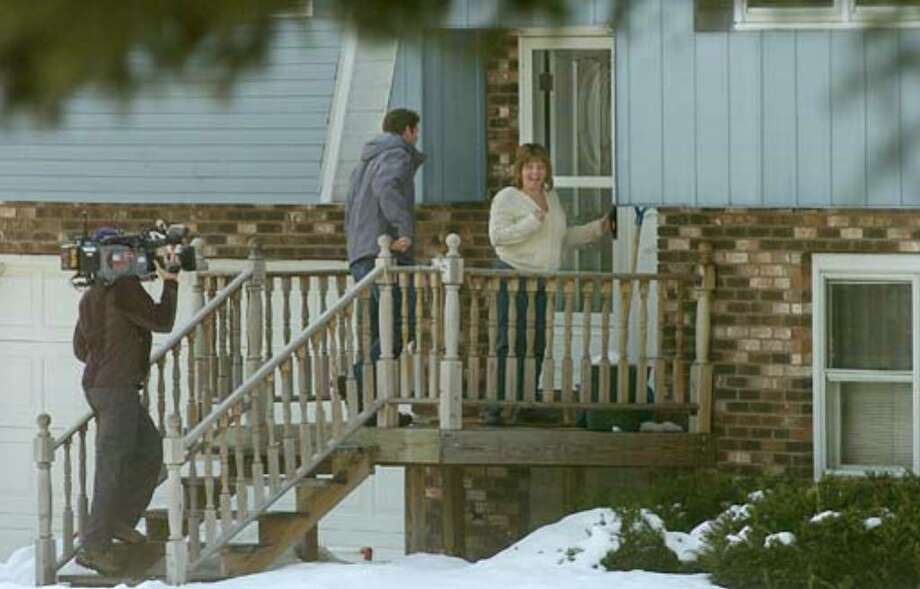 """A cameraman from ABC's """"Extreme Makeover: Home Edition"""" follows the show's host, Ty Pennington, and Debbie Oatman up the stairs of Oatman's home on Fairway Lane in Colonie after she found out that her home will be razed and rebuilt. Photo: Paul Buckowski"""