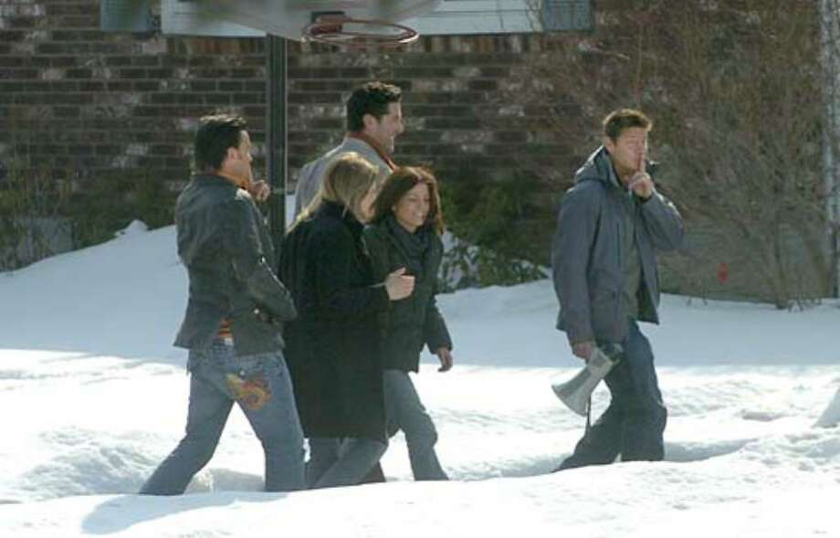 """Extreme Makeover: Home Edition"" design team members, from left, Michael Moloney, Tracy Hutson, Eduardo Xol, Tanya McQueen and Ty Pennington sneak up to the home of Debbie Oatman on Fairway Lane in Colonie on Thursday, March 22, 2007.  Oatman's home will be razed and rebuilt by the show's crew and local volunteers. Photo: Paul Buckowski"