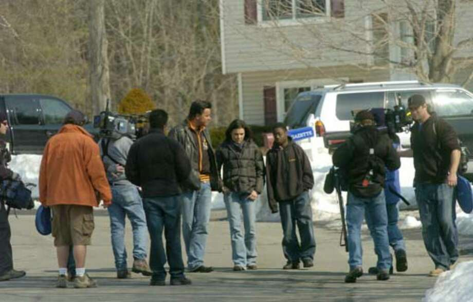 """Extreme Makeover: Home Edition"" designers Michael Moloney, center left, and Tanya McQueen talk with Debbie Oatman's son, Kevin, as they are filmed by the show's crew outside the Oatman family's home on Fairway Lane in Colonie on Thursday, March 22, 2007. Photo: Paul Buckowski"