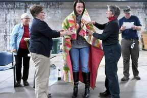 Air Force veteran and AMR payroll manager Rachel O'Neill (center) is wrapped in a hand-made quilt from Quilts of Valor by Nancy Olson (left) and Jane Dougherty, Connecticut Co-Coordinator of the Quilts of Valor Foundation, during a ceremony following a breakfast for veterans at American Medical Response headquarters in New Haven on November 9, 2018.