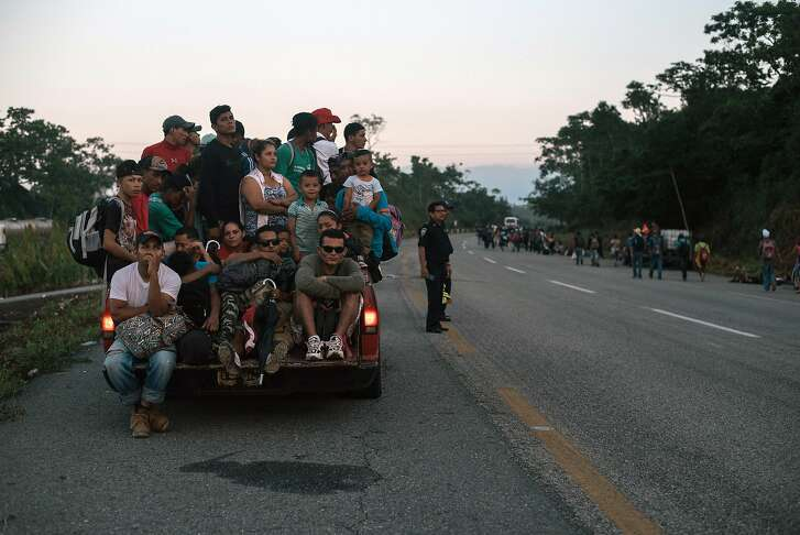 A group of migrants from Central America riding in the back of a truck on the outskirts of Huixtla, Mexico, wait to proceed on their journey north, on Oct. 24, 2018. President Donald Trump proclaimed on Nov. 9 that the illegal entry of immigrants across the southern border of the U.S. is detrimental to the national interest, triggering tough changes that will deny asylum to all migrants who do not enter through official border crossings. (Luis Antonio Rojas/The New York Times)
