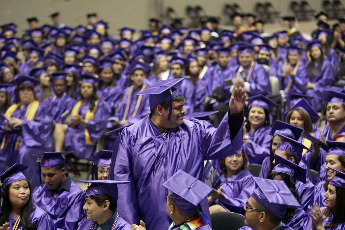 Dylan Barrera waves to those inside the Freeman Coliseum as he is acknowledged by the Northwest Vista College president May 14, 2014 during graduation. Community colleges generally give non-traditional students in particular a shot at a college education.