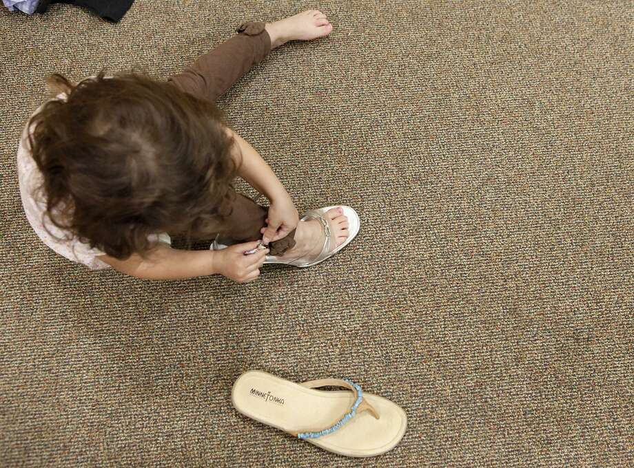 A child tries on shoes at the Battered Women and Children's Shelter. Domestic violence does not spare any demographic, including the LGBTQ community. Photo: File Photo / For San Antonio Express-News