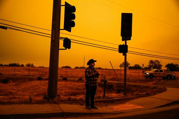 Evacuee Jonathan Taylor stands on the road to take photos of the Camp Fire in Paradise, California, on Friday, Nov. 9, 2018. His house and family business are in Paradise and he is concerned they will be gone when he goes back home.