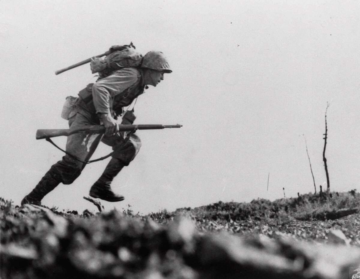 """A U.S. Marine from the 6th Marine Division charges forward through Japanese machine gun fire in """"Death Valley,"""" April 12, 1945, where Leathernecks lost 125 men in eight hours of sustained fighting on Okinawa. Our veterans' war stories contain meaning."""
