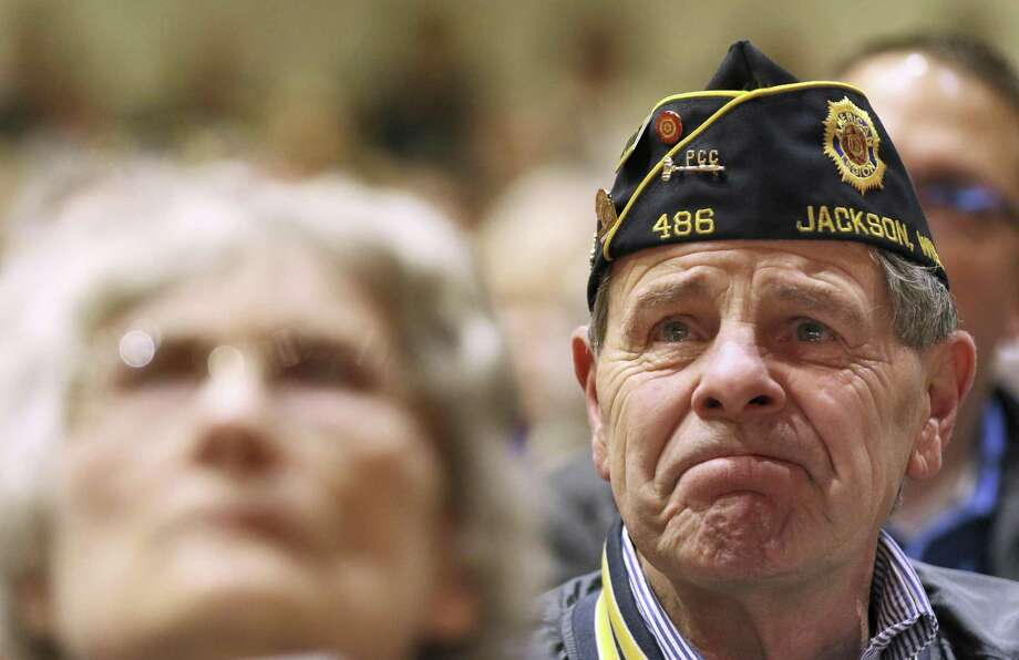 "United States Army veteran Bob Bliese of Jackson listens to ""Got Your Back,"" by Autumn Parker read during the Veterans Day program on Thursday at Kettle Moraine Lutheran High School in Jackson, Wis. Photo: John Ehlke /Associated Press / Conley Publishing"