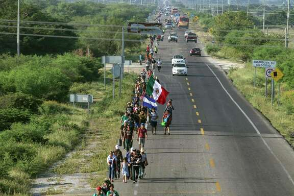 Migrants — mostly Hondurans — taking part in a caravan heading to the US, hold Honduran and Mexican national flags as they walk along the road on their way to Matias Romero, at La Ventosa, Oaxaca State, Mexico, on Nov. 1. A reader says that this is, indeed, an invasion.