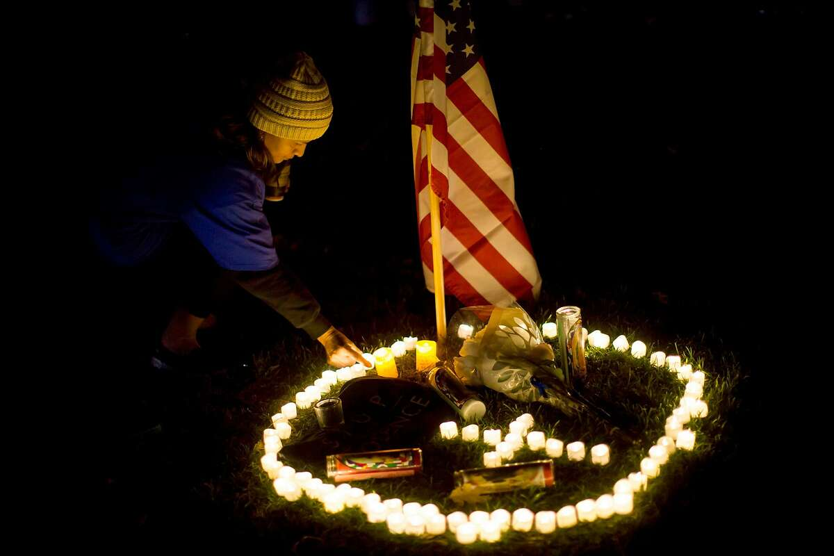 A woman places a candle on the grass during a vigil to pay tribute to the victims of a shooting in Thousand Oaks, California, on November 8, 2018. - A 28-year-old US Marine Corps combat veteran opened fire in a crowded country music bar in California, killing 12 people including a police officer who rushed in and exchanged shots with the gunman, authorities said. (Photo by Apu Gomes / AFP)APU GOMES/AFP/Getty Images