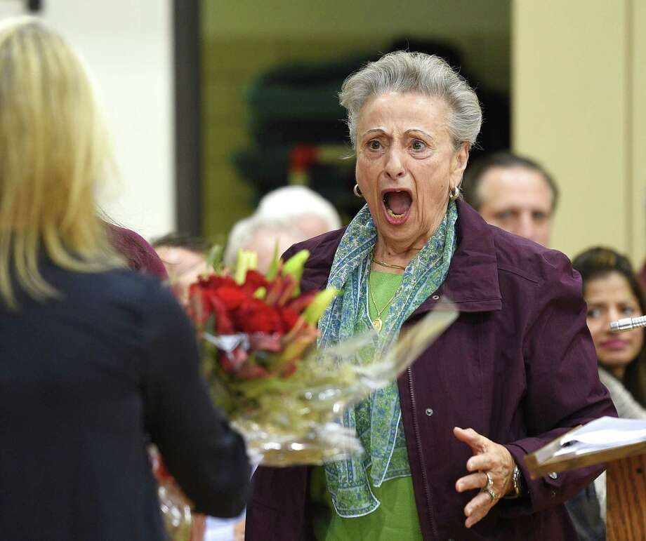 Nancy Mecca, wife of the late Riverside veteran Nick Mecca, is shocked to receive a bouquet of flowers at the Veterans Day ceremony at Riverside School in the Riverside section of Greenwich, Conn. Friday, Nov. 9, 2018. The ceremony featured a slideshow and musical performances to honor veterans, including the late Nick Mecca, a longtime Riverside resident and school crossing guard. Photo: Tyler Sizemore / Hearst Connecticut Media / Greenwich Time