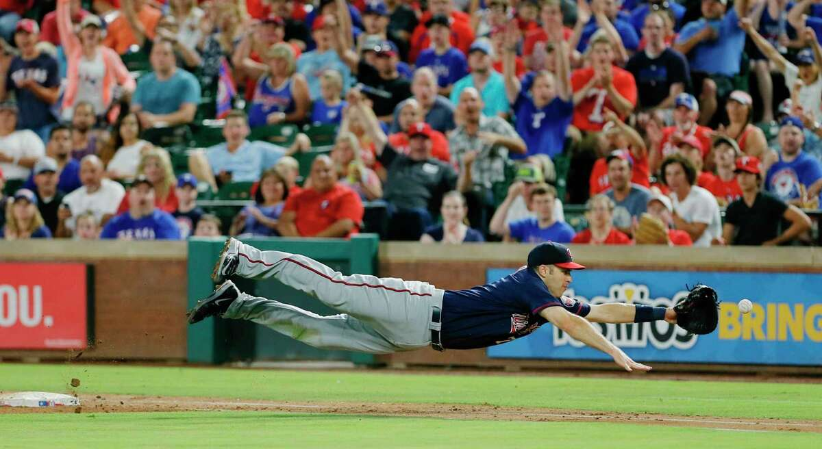 FILE - In this Saturday, July 9, 2016, file photo, Minnesota Twins first baseman Joe Mauer dives for a bad throw from second baseman Brian Dozier during the second inning of a baseball game against the Texas Rangers in Arlington, Texas. The Minneapolis Star Tribune reports that Mauer has taken out an ad in its Sunday, Nov. 11, 2018, paper to announce his retirement.