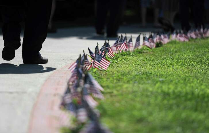 Memorial attendees walk by a row a flags during the Korean War Memorial Ceremony at Rogers Park in Danbury, Conn. on Saturday, July 27, 2013. The ceremony celebrated the 60th anniversary of the armistace, thanking those who fought and remembering those who died during the Korean War.