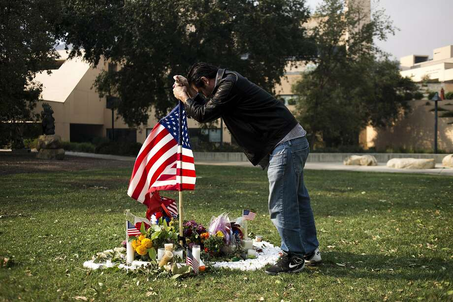 Alfonso Gonzalez places a U.S. flag Friday at a memorial dedicated to victims of a mass shooting at a nearby bar outside City Hall in Thousand Oaks. Photo: Jenna Schoenefeld / New York Times