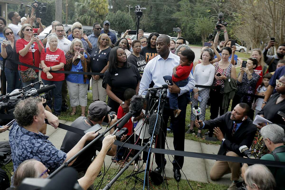 Florida gubernatorial Democratic candidate and Tallahassee Mayor Andrew Gillum takes questions from the press while his wife R. Jai Gillum, and their three children look on after casting their ballots at the Good Shepherd Catholic Church Precinct in Tallahassee, Florida on Tuesday, November 6, 2018. (Octavio Jones/The Tampa Bay Times via AP)