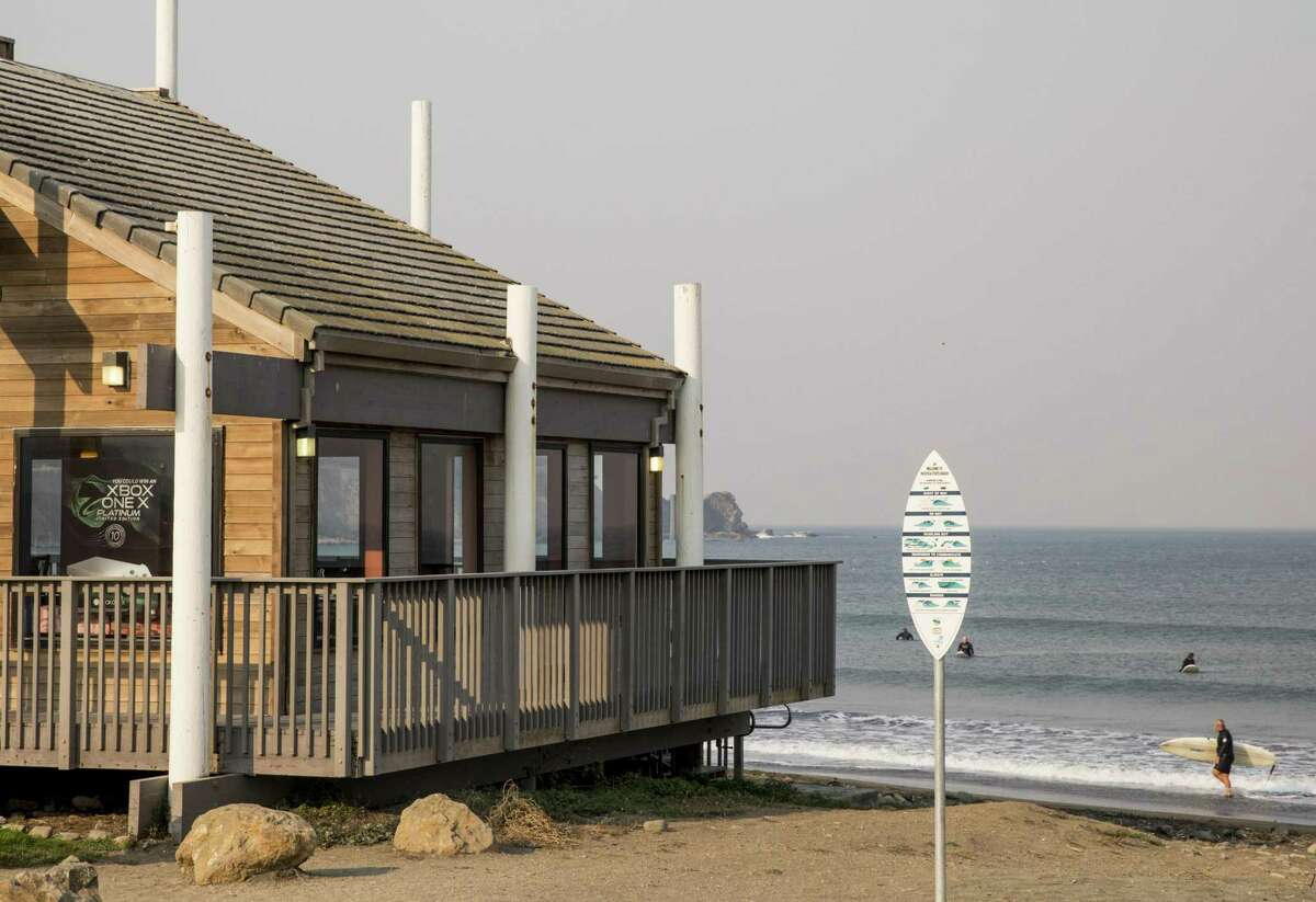 A surfer exits the water, right, near the Taco Bell located on the shores of Pacifica State Beach.