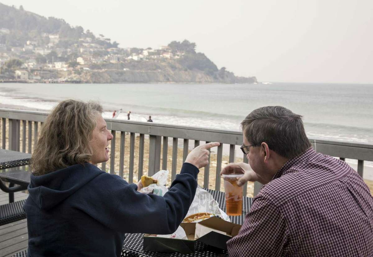 Peggy and Mike Bowles of Modesto enjoy a meal while watching surfers on the back deck of Taco Bell located on the shores of Pacifica.