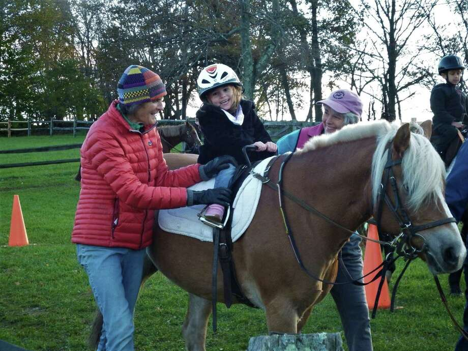 Isabella Pelosi rides pony Bobbie, assisted by Little Britches vice president Stuart Daly, left, and occupational therapistCindy Winton-Bunting. Photo: Contributed Photo