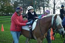 Isabella Pelosi rides pony Bobbie, assisted by Little Britches vice president Stuart Daly, left, and occupational therapistCindy Winton-Bunting.