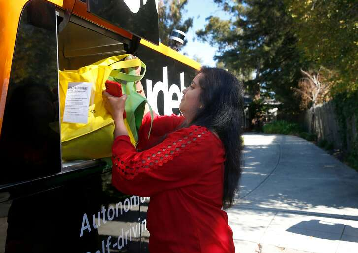 Anitha Arackaparampil removes groceries from Farmstead delivered to her home by a Udelv autonomous van in Burlingame, Calif. on Wednesday, Nov. 7, 2018. Udelv's four driverless vans provide delivery service for several vendors and hopes to have a fleet of 100 vehicles by sometime next year.
