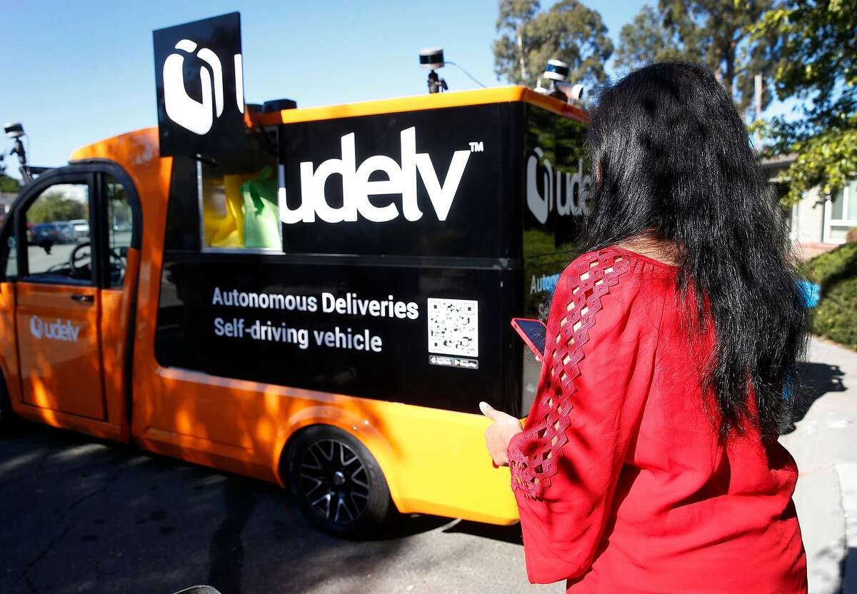 Anitha Arackaparampil uses an app to retrieve groceries from Farmstead on a Udelv autonomous delivery van in Burlingame, Calif. on Wednesday, Nov. 7, 2018. Udelv's four driverless vans provide delivery service for several vendors and hopes to have a fleet of 100 vehicles by sometime next year.