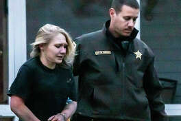 A Madison County deputy Thursday escorts Tricia Grass to a police vehicle after her arrest Thursday near Route 159 and Midway Drive northeast of Bethalto. Deputies say she escaped a squad car, while handcuffed and eluded police for nearly an hour before being tracked down by an Alton K-9. She wanted on a warrant for skipping bond on a previous charge escaping police custody, as well as drug charges.