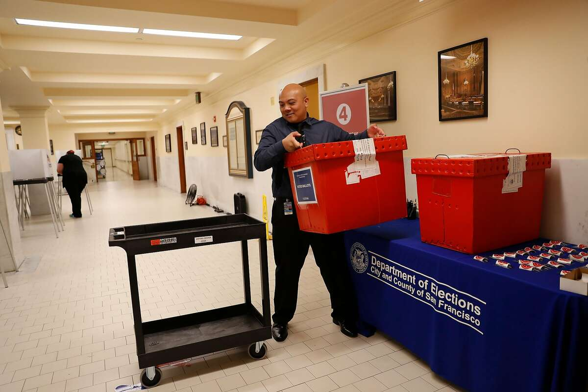 A Department of Elections worker moves a full ballot box during early voting at City Hall in San Francisco, Calif. on Monday, Nov. 5, 2018.