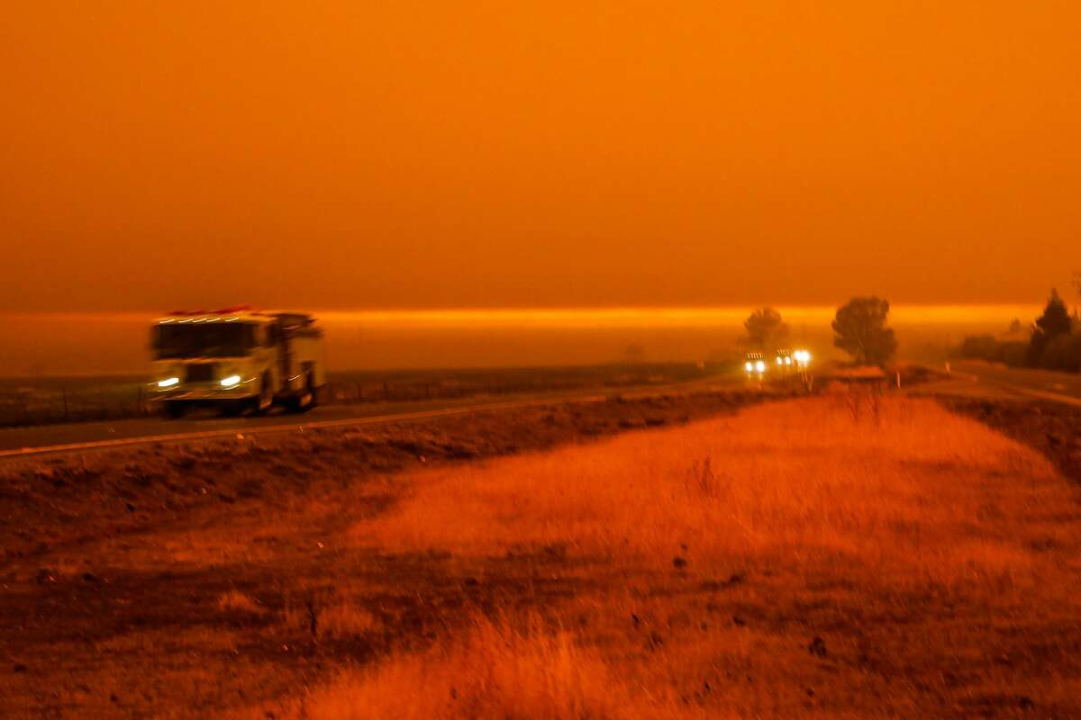Cars pass Skyway highway during the Camp Fire in Paradise, California, on Friday, Nov. 9, 2018.