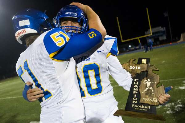 Midland senior Christian Gordon, right, and senior James Harris, left, embrace after being awarded the trophy for their District 2 regional championship win over Walled Lake Western on Friday, Nov. 9, 2018 at Walled Lake Western High School. (Katy Kildee/kkildee@mdn.net)