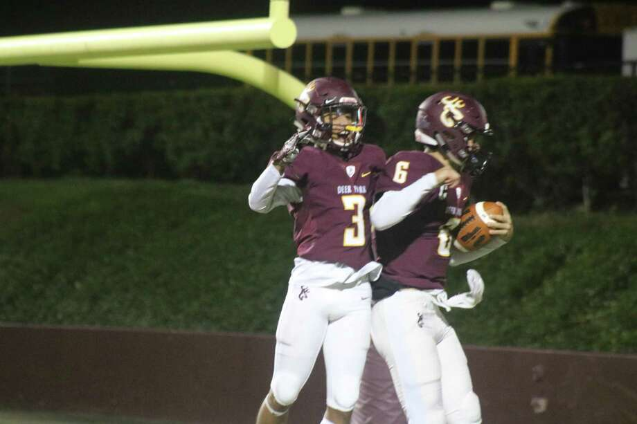 Deer Park quarterback Broc Weidner (right) and Clyde Bellow celebrate the night's first touchdown, a 22-yard run by the Deer quarterback just 1:09 into the contest. Photo: Robert Avery