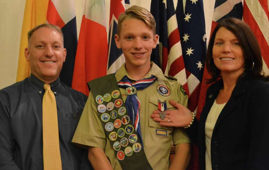 Evan Piscitelli, center, of Troop 1 in Ballston Spa, received his Eagle Scout Award at the Ballston Spa United Methodist Church. He is joined by father Mike Piscitelli and mother Karen. His project took place at the Malta Ecological Park where he planted lupine, milkweed and wild flowers in the giant grass circle at the entrance to the park to attract Monarch and Karner Blue butterflies which threaten of being endangered.