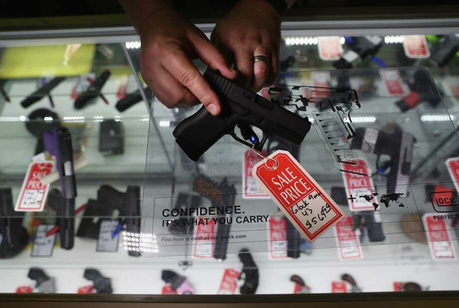 BENSON, AZ - SEPTEMBER 29:  Gun shop owner Jeff Binkley displays a Glock 9mm pistol at Sarge's Sidearms on September 29, 2016 in Benson, Arizona. He said he redesigned and renamed his store just this year. Gun shops are proliferate in Arizona, which regulates and restricts weapons less than anywhere in the United States.  (Photo by John Moore/Getty Images) ORG XMIT: 672145955 Photo: John Moore / 2016 Getty Images