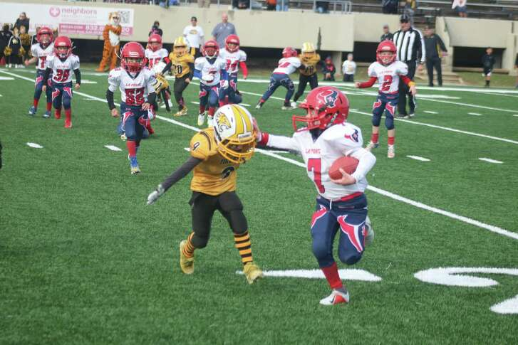 La Porte Texans ballcarrier Charlie Gale stiff-arms Deer Park Tiger Harper Wilson en route to another big gain in the Pee Wee Super Bowl at Stallworth Stadium.