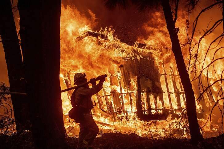 Firefighter Jose Corona sprays water as flames consume from the Camp Fire consume a home in Magalia, Calif., on Friday, Nov. 9, 2018. (AP Photo/Noah Berger)