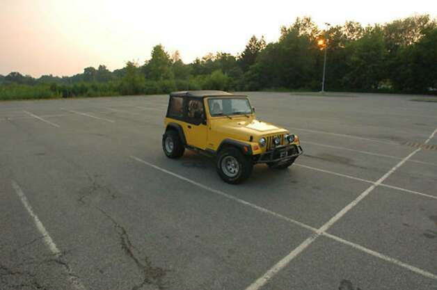 Christopher Porco's yellow Jeep sits alone in the lot at the Orange County Courthouse in Goshen, on Thursday, August 10, 2006. Photo: Michael P. Farrell