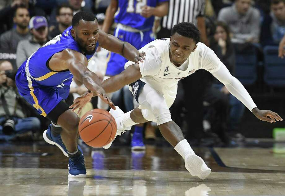 Morehead State's A.J. Hicks, left, and UConn's Christian Vital, right, chase down a loose ball during the first half on Thursday. Photo: Jessica Hill / Associated Press / Copyright 2018 The Associated Press. All rights reserved