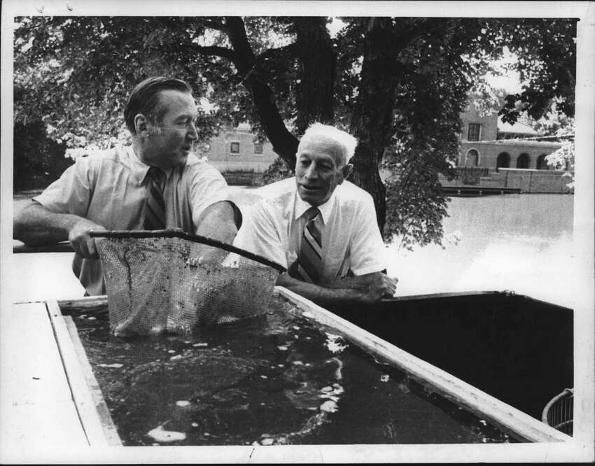 Albany, New York - State Department of Environmental Conservation Commissioner Robert Flacke, left, checks over bullheads with the help of Albany Mayor Erastus Corning as they prepare to stock Washington Park Lake. February 21, 1979 (Fred McKinney/Times Union Archive)