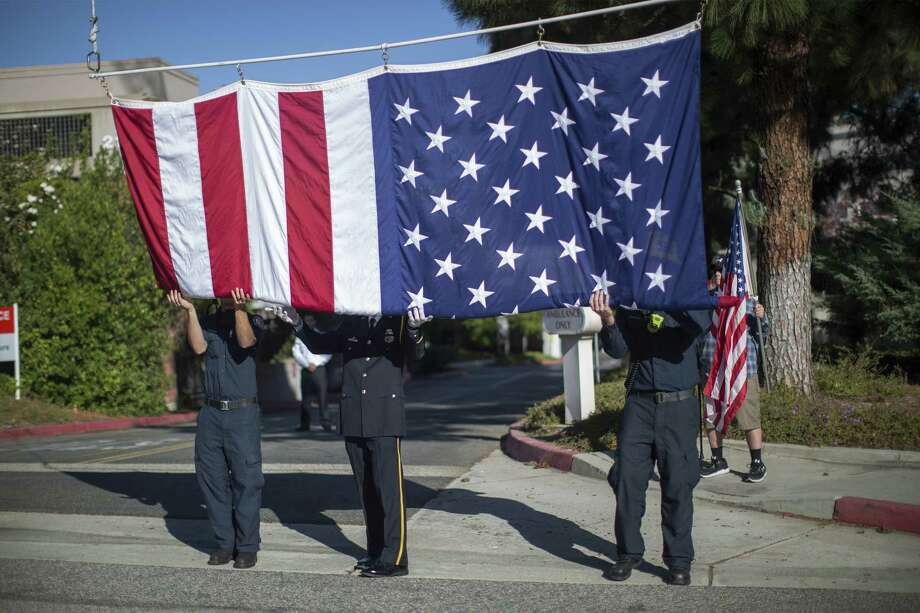 THOUSAND OAKS, CA - NOVEMBER 08: Firefighters raise a flag at Los Robles Hospital to hang over the procession carrying the body of Ventura County Sheriff Sgt. Ron Helus, who was killed in a mass shooting at the Borderline Bar and Grill, on November 8, 2018 in Thousand Oaks, California. 12 people have died including the sergeant plus the gunman.  (Photo by David McNew/Getty Images) *** BESTPIX *** Photo: David McNew / 2018 Getty Images