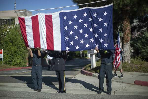 THOUSAND OAKS, CA - NOVEMBER 08: Firefighters raise a flag at Los Robles Hospital to hang over the procession carrying the body of Ventura County Sheriff Sgt. Ron Helus, who was killed in a mass shooting at the Borderline Bar and Grill, on November 8, 2018 in Thousand Oaks, California. 12 people have died including the sergeant plus the gunman. (Photo by David McNew/Getty Images) *** BESTPIX ***