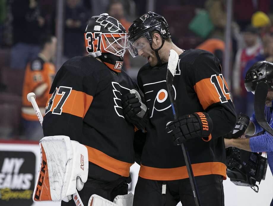 Flyers goalie Brian Elliott (left), who had a shutout, and Sean Couturier, who scored two goals, congratulate each other. Photo: Chris Szagola / Associated Press
