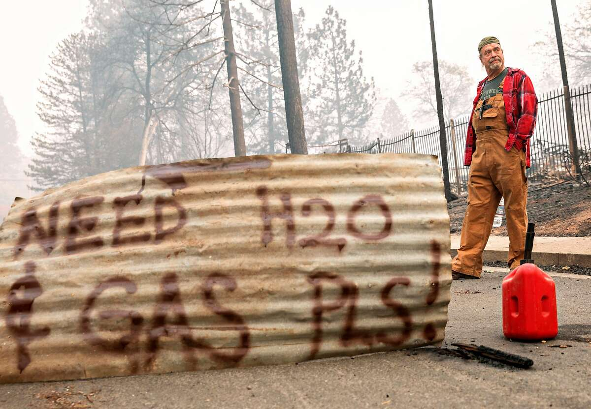 """Brad Weldon stands by a sign he made that reads """"Need H20 & Gas Pls!"""" hoping for assistance after the Camp Fire devastated the entire town of Paradise, Calif. Saturday, Nov. 10, 2018. Weldon stayed in his home with his 90-year-old mother, Norma Weldon, and roommate, Mic McCrary, as the fire overtook their entire neighborhood while leaving his home untouched."""